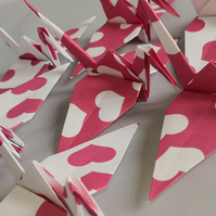 20 Origami Cranes with a pink love heart print.