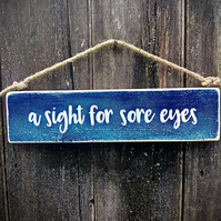 Handmade wooden sign with the words 'a sight for sore eyes'.
