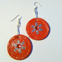 red clay circle earrings with silver snowflake and red 'jewel'