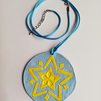 Blue circle pendant with yellow star motif