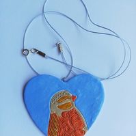 Heart pendant with bird motif on sky blue background