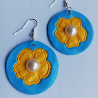 Canary yellow flowers on a sky blue background with central pearl cabochon