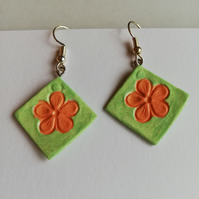 Green earrings showing orange flowers