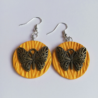 Butterfly earrings on orange background