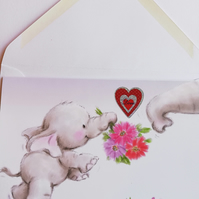 Blank card showing baby elephant with bouquet and heart
