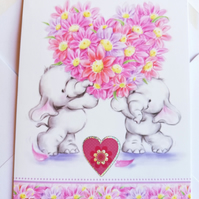 Blank birthday card with baby elephants, flowers and heart.