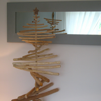 A contemporary stripped-wood Christmas tree sculpture topped with a star.