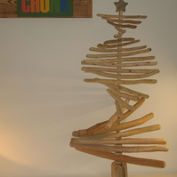 A contemporary stripped-wood Christmas tree topped with a driftwood star.