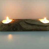 A rustic wooden holder for two tealight candles