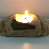 A rustic wooden holder for one tealight candle