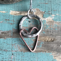 Hammered silver ring and copper heart necklace.