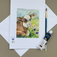 Watercolour painted card of cow in field of purple clover.