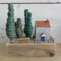 Small wooden house and a wooded area - scene from reclaimed materials