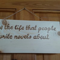 Hanging wall door plaque 'Live the life people write novels about' in pyrography