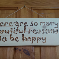 Wall or door plaque 'There are so many reasons to be happy' in pyrography