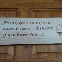 Hanging wall plaque 'Friends don't care if your house....' done in pyrography