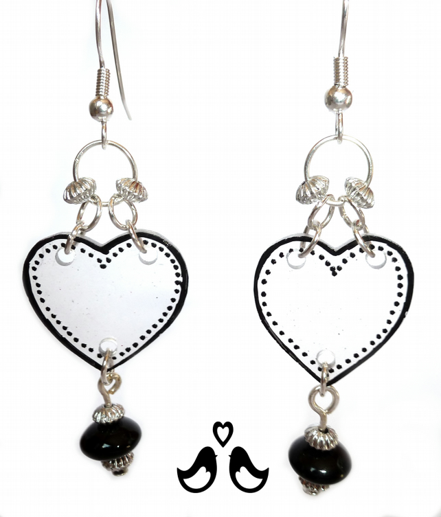 Black heart design dangle earrings, hand coloured on transparent plastic.