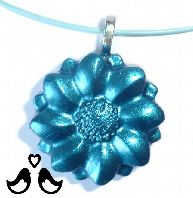 Royal blue flower pendant on blue steel hoop necklace.