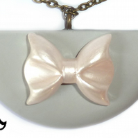 Semicircle pendant in a soft grey colour with an ivory lustre bow detail.