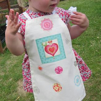 Pretty apron with heart motif for a toddler