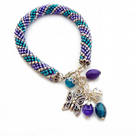 Bracelet made of glass beads - purple, turquoise, silver, butterfly