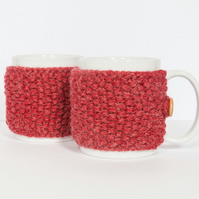Pair of knitted mug cosies, cup cosy, coffee cosy in red. Coffee mug cosy