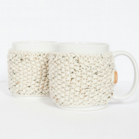 Pair of knitted mug cosies, cup cosy, coffee cosy in oatmeal. Coffee mug cosy