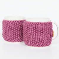Pair of knitted mug cosies, cup cosy, coffee cosy in berry. Coffee mug cosy