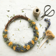 A Unique Dried Flower Wreath crafted using soft blues and yellow tones