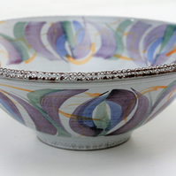 Ceramic serving bowl in purples and greens