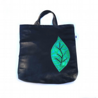 Black faux suede tote bag with green vintage fabric leaf embellishment