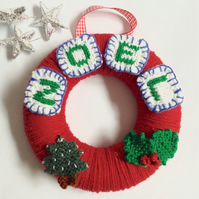 Red wool Christmas wreath with knitted decorations