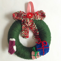 Green wool Christmas wreath with knitted decorations