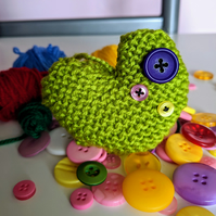 Hand-knitted bright green button heart