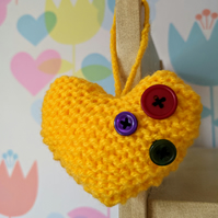 Hand-knitted yellow button heart