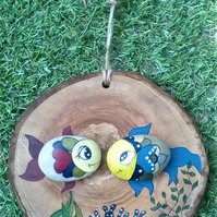 Two little Fish hand painted on pebbles and set on a hanging wooden roundel.
