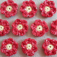 10 hand crocheted flowers with yellow middles and red variegated petals