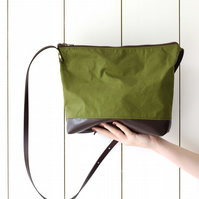 Green canvas cross body bag with leather base and leather adjustable straps