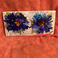 Vivid blue and purple alcohol ink flowers on ceramic tile.