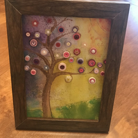 A hand painted tree with quilled decoration, in a wooden frame.