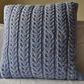 Blue hand knitted lobster claw cable cushion made from aran wool