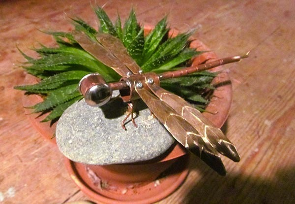 Eco friendly copper Dragonfly on pebble.