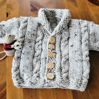 Knitted Aran baby cardigan with shawl collar and cable pattern.