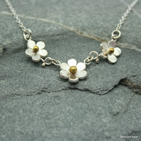 Sterling silver, three daisy necklace with brass bead centres.