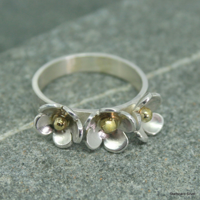 Sterling silver three daisy ring with brass bead centres on flat silver band