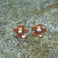 Copper daisy stud earrings with sterling silver posts and scroll ear fittings.