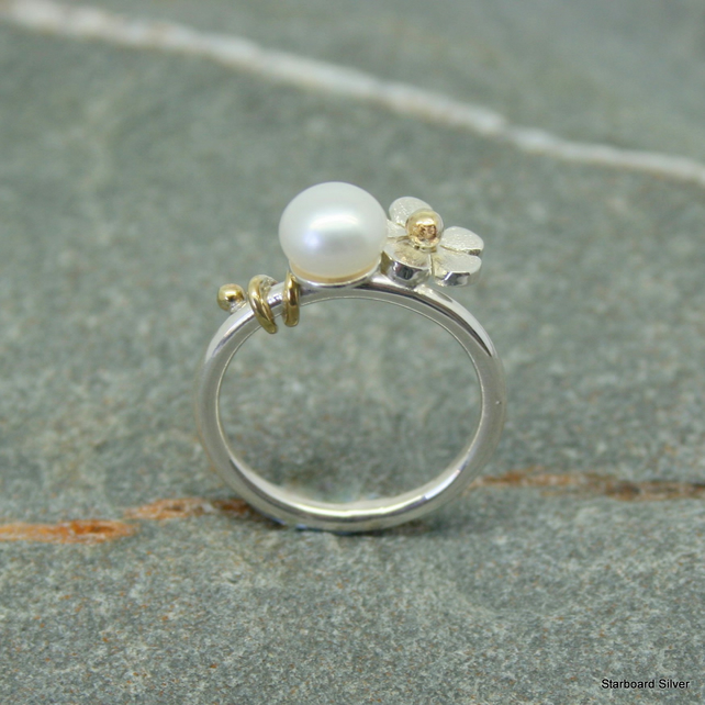 Sterling silver pearl ring with single daisy and brass detail.