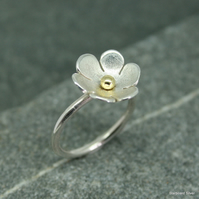 Stering silver daisy ring with brass bead centre.