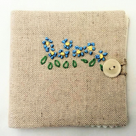 Sewing needle case with hand embroidered flowers.