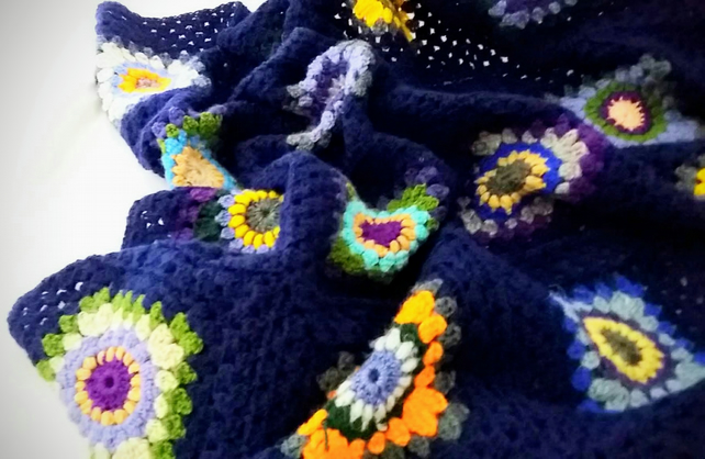 Crochet blanket in bright and cheerful colours set in navy blue.